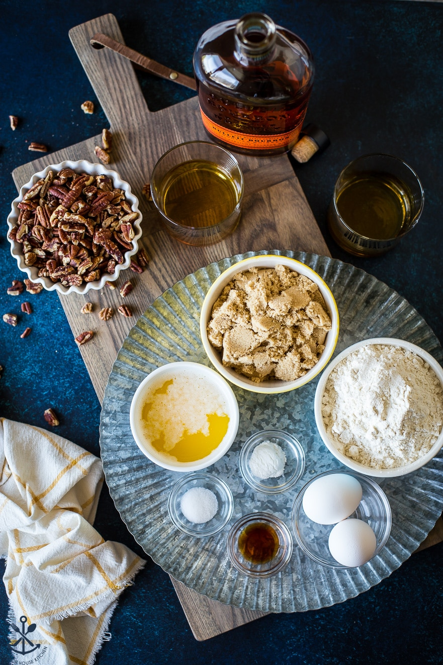 Overhead photo of ingredients for pecan bourbon blondies on a silver tray on a wooden board
