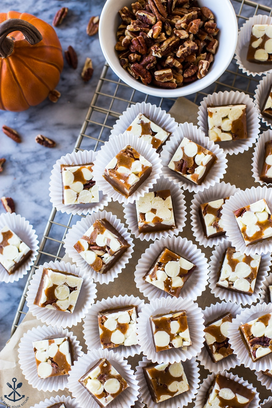 Pumpkin Spice White Chocolate Pecan Caramels on a marble board with a white dish of pecans