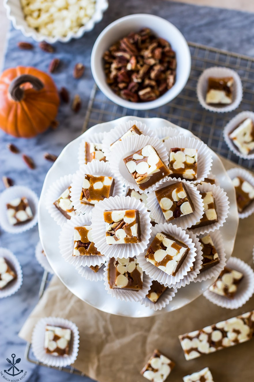 Overhead photo of caramels on a white plate with a bowl of pecans