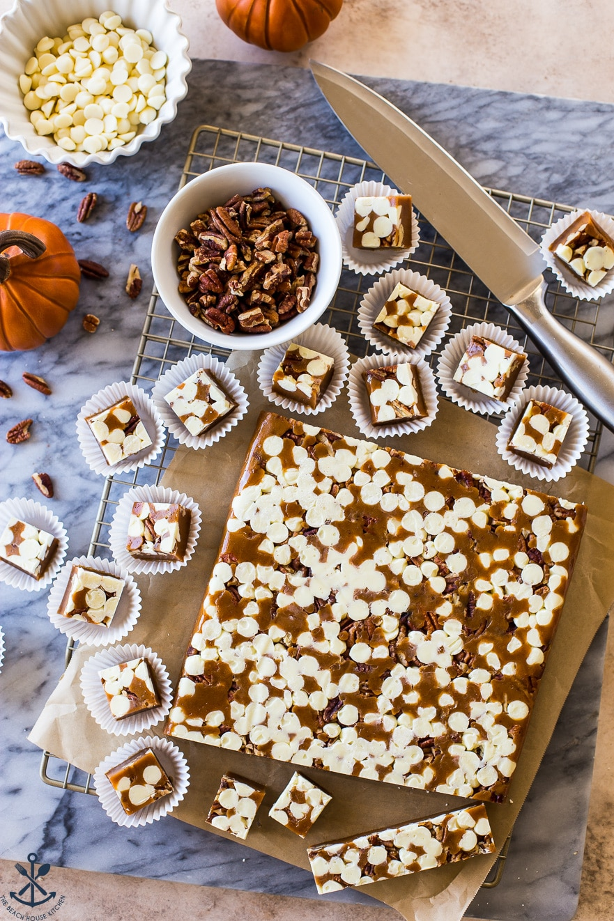 Overhead photo of marble board with Pumpkin Spice White Chocolate Pecan Caramels in a slab and in white paper cups
