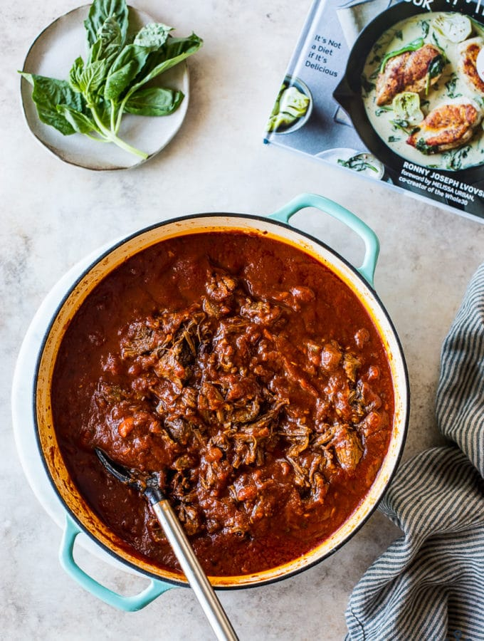 Short Rib Ragù in a Dutch oven with a small plate of basil leaves