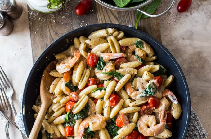 Overhead photo of skillet filled with Shrimp Pasta with Garlic Cream Sauce Tomatoes and Spinach