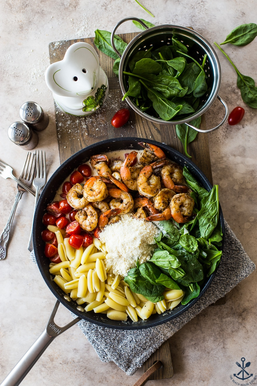 Overhead photo of skillet filled with ingredients for Shrimp Pasta with Garlic Cream Sauce Tomatoes and Spinach