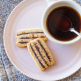 Overhead photo of cherry ribbon butter cookies on a pink plate with a cup of coffee