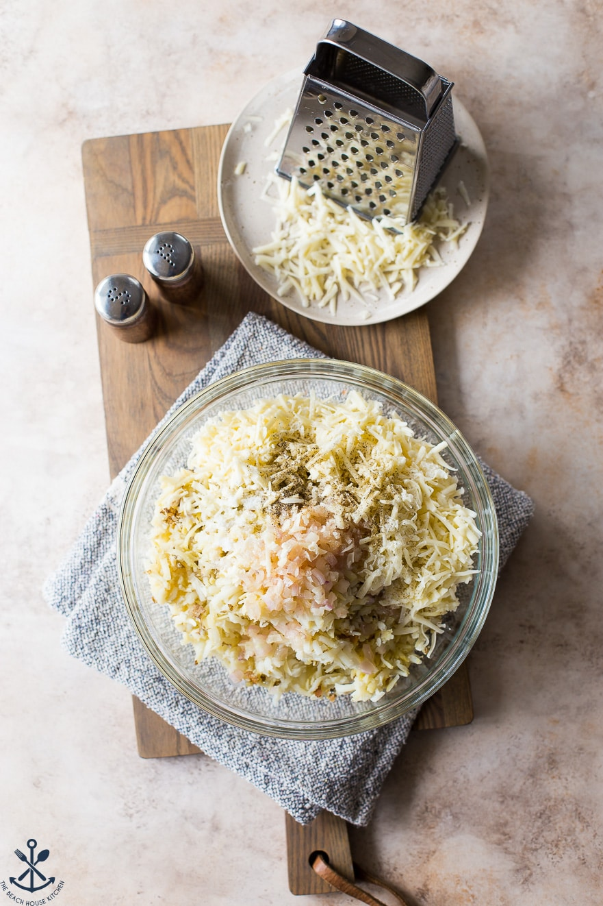 Overhead photo of ingredients for potato dish in a glass bowl with a plate of shredded cheese and a grater