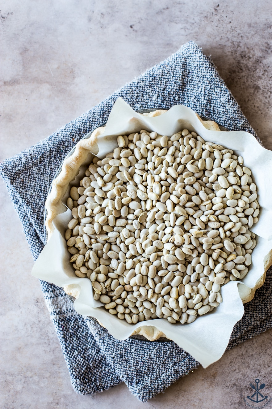 Overhead photo of pie shell lined with parchment paper and dried beans