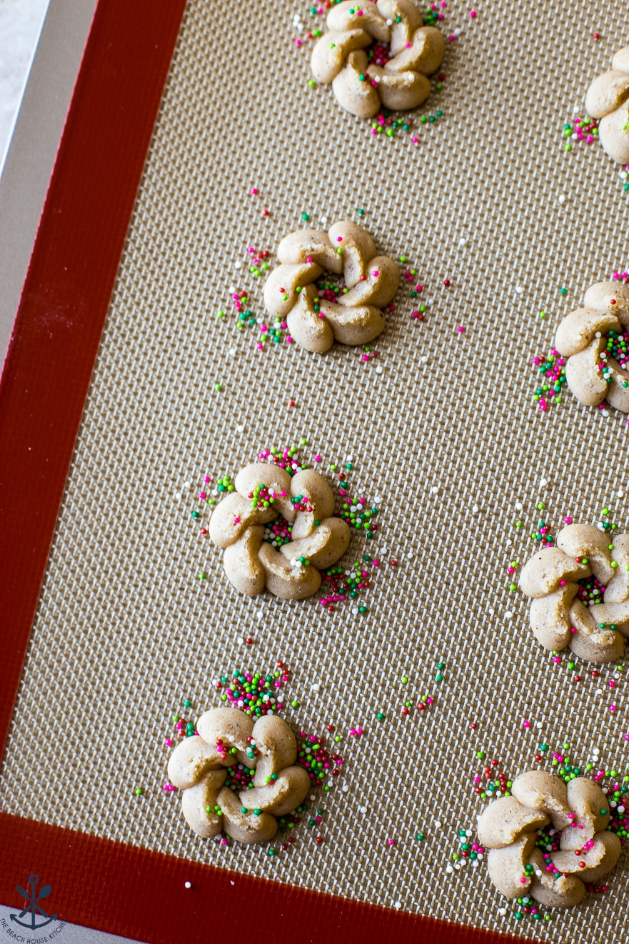 Pre-baked Chai Spiced Spritz Cookies on a silpat mat lined baking sheet