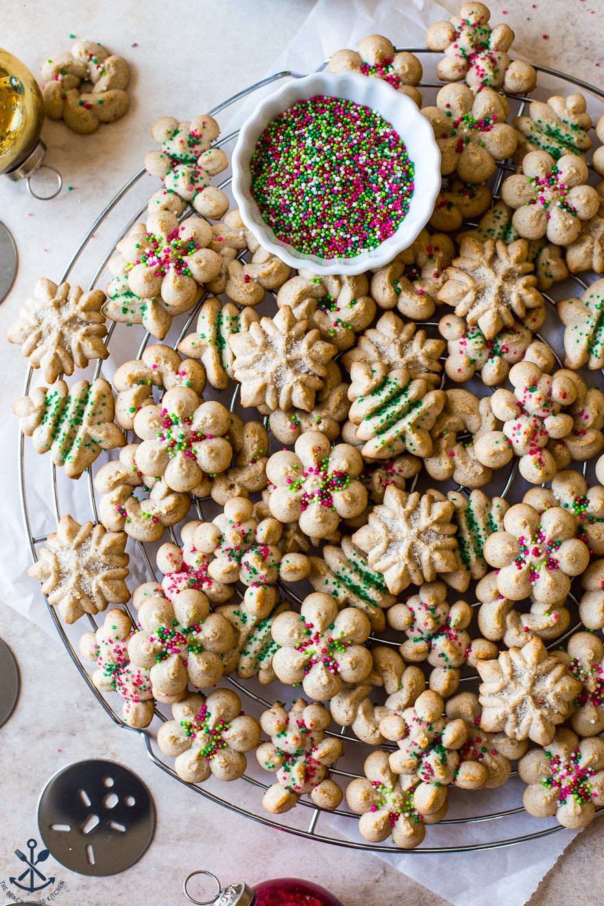 Overhead photo of spritz cookies on a round wire rack with a small bowl on colored non pariels