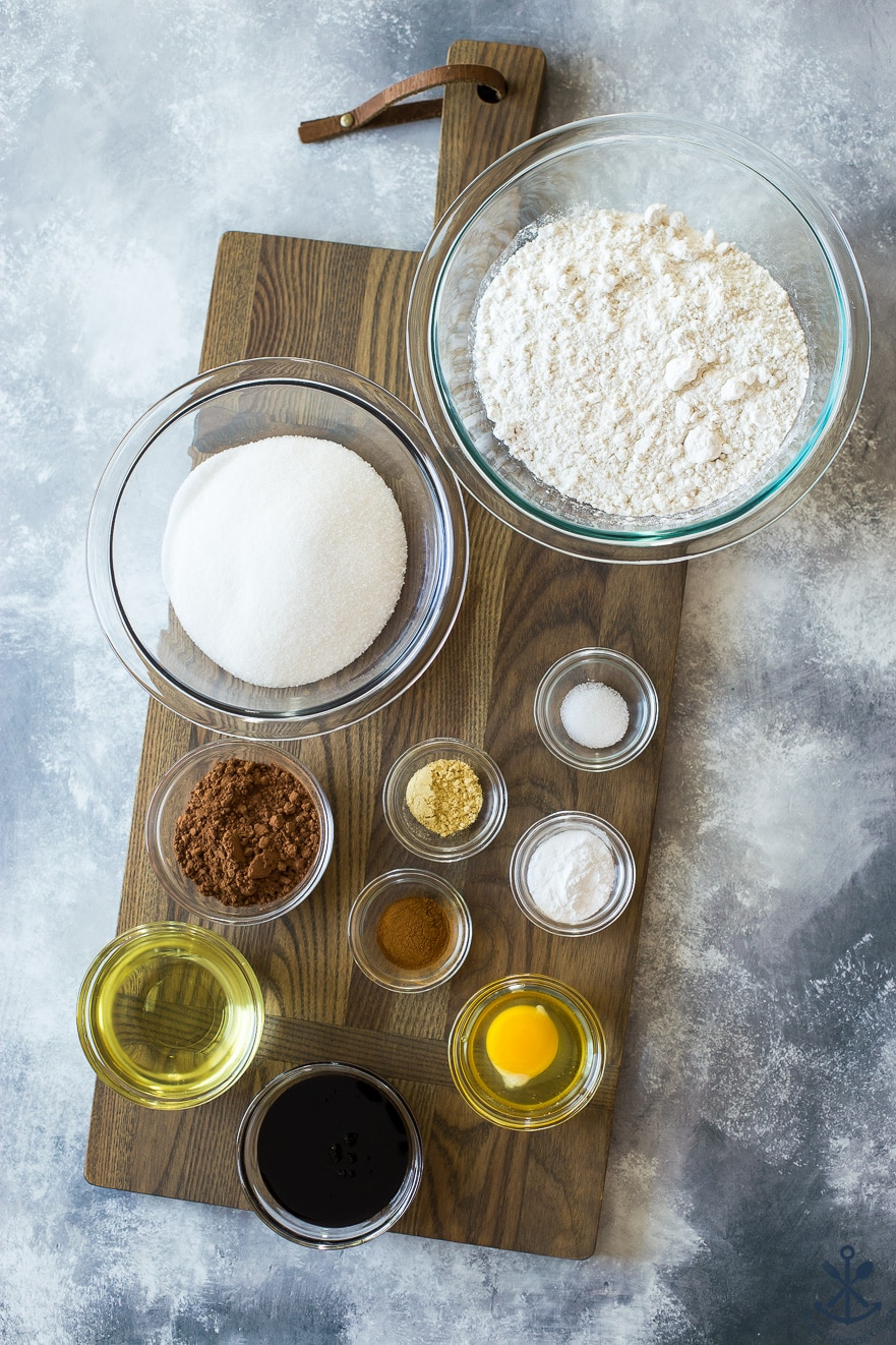 Ingredients for cookies in indivial glass bowls on a wooden board