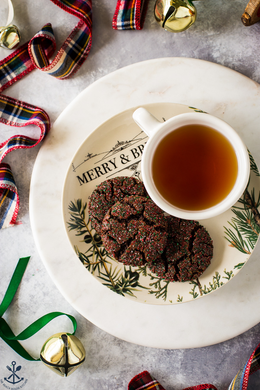 Overhead photo of a plate of 3 chewy chocolate gingersnap cookies with a cup of tea