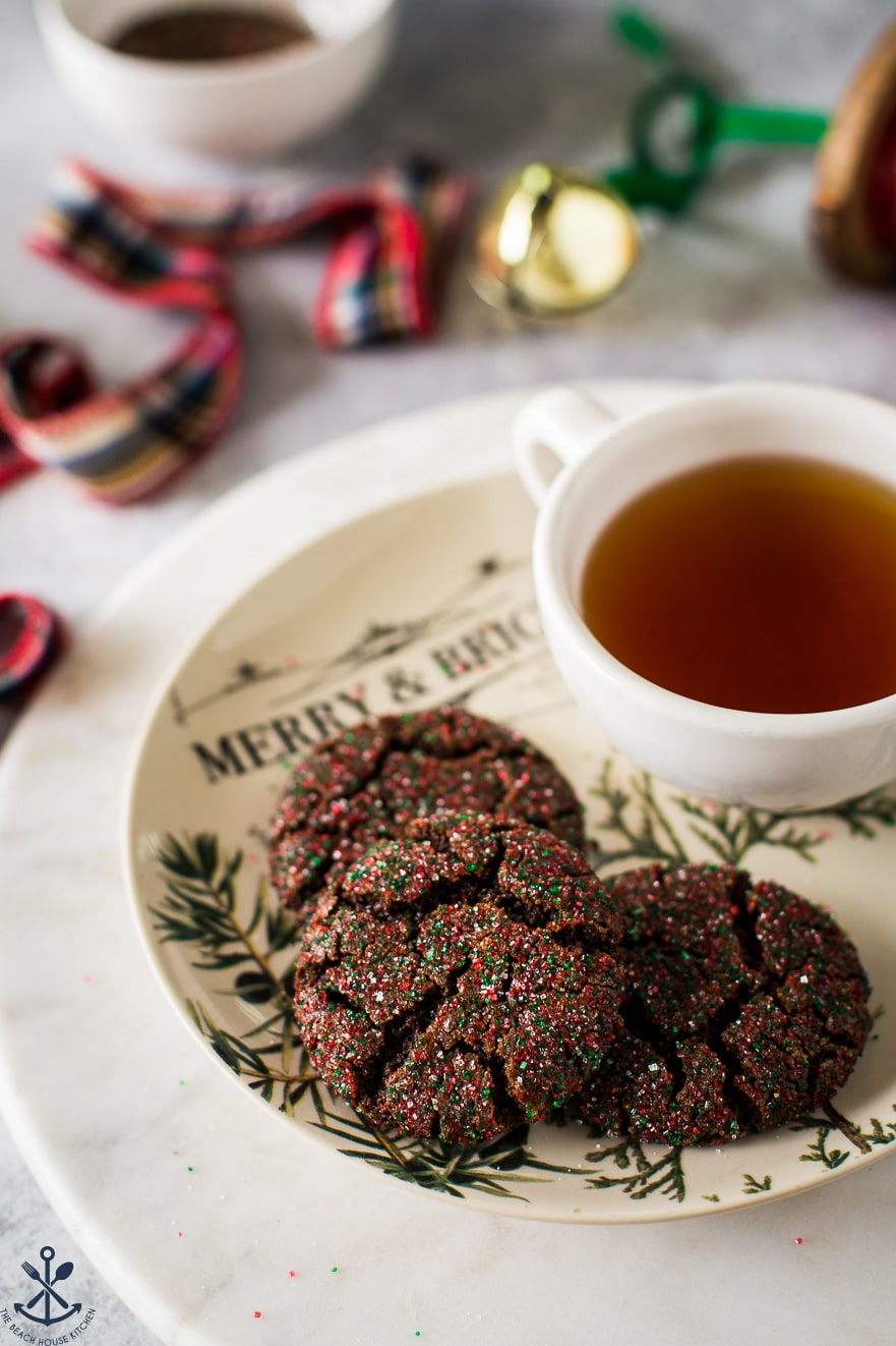 A plate of chocolate gingersnap cookies with a cup of tea