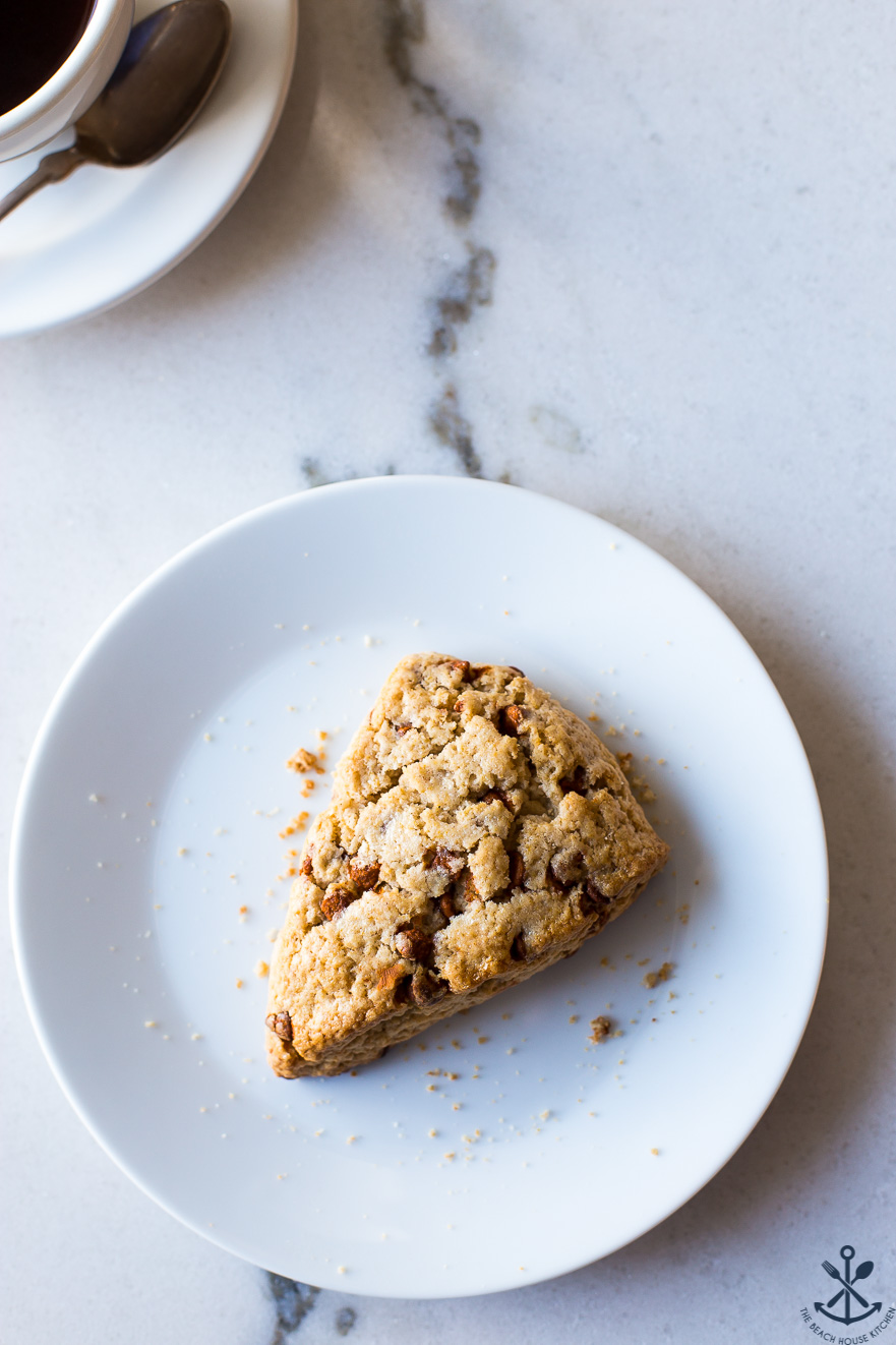 Overhead photo of a cinnamon chip scone on a white plate on a marble board