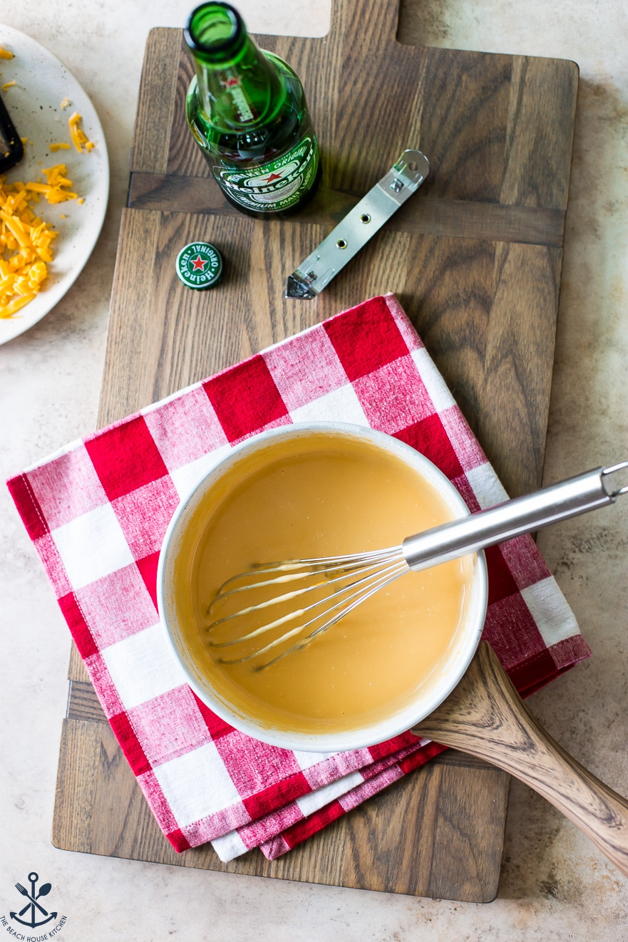Overhead photo of saucepan filled with cheese dip and a whisk
