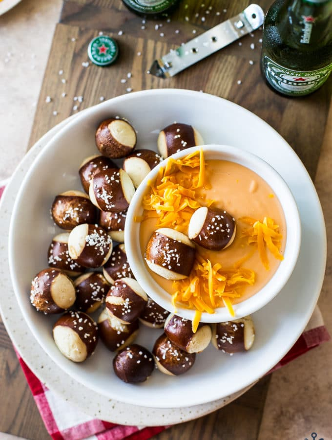 Easy Creamy Beer Cheese Dip in a bowl surrounded by pretzel nuggets