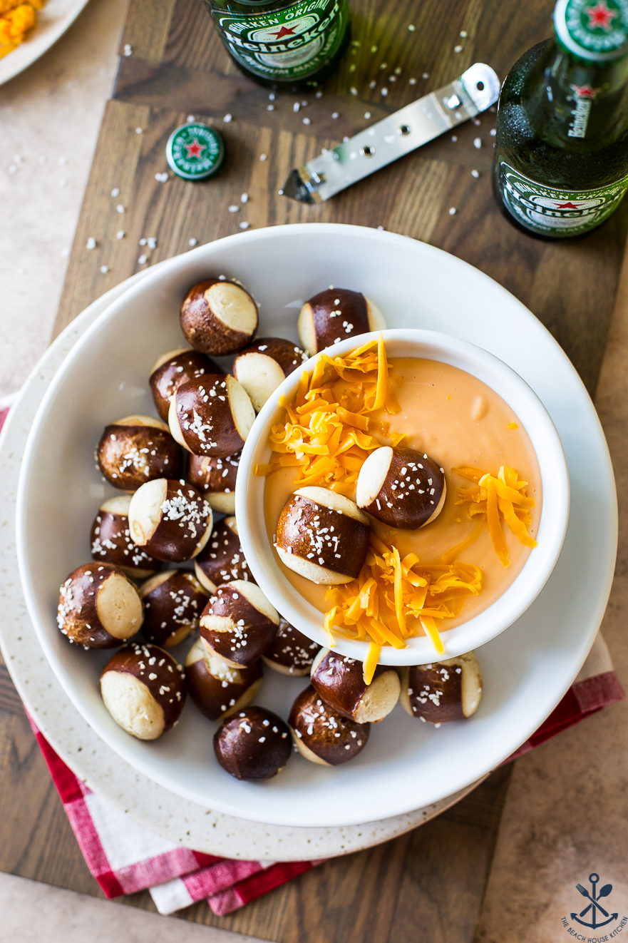Overhead photo of cheese dip in a bowl surrounded by pretzel nuggets
