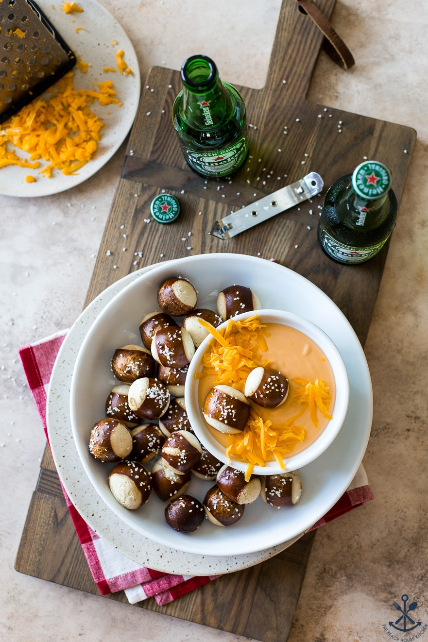 Overhead photo of easy creamy beer cheese dip in a bowl surrounded by pretzels