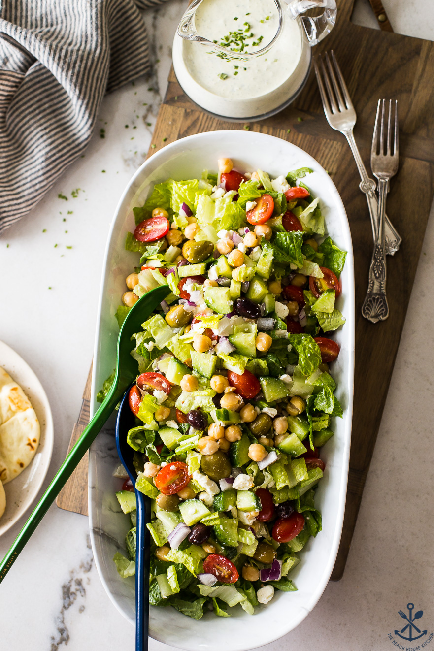 Overhead photo of Greek Chickpea Salad with Green Goddess Dressing in an oval bowl on a wooden board