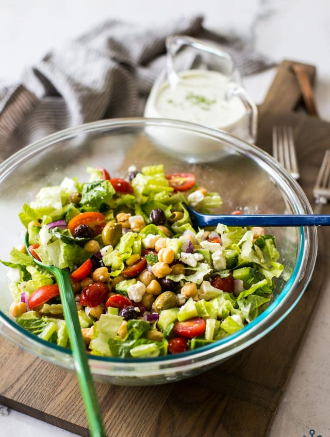 Greek Chickpea Salad with Green Goddess Dressing in a bowl on a wooden board with dressing in a glass pitcher in the background
