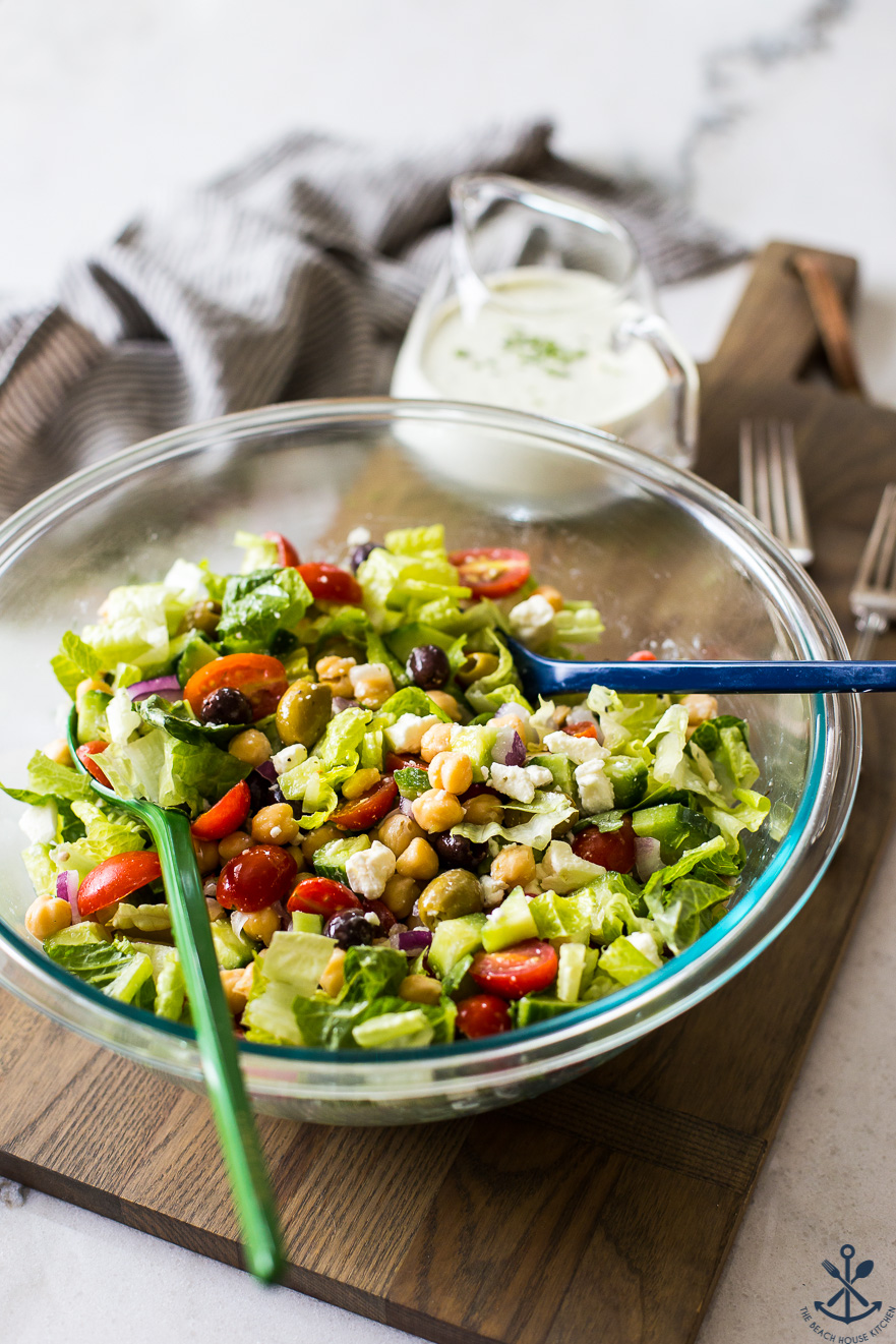 Chickpea salad in a bowl on a wooden board with dressing in a glass pitcher in the background
