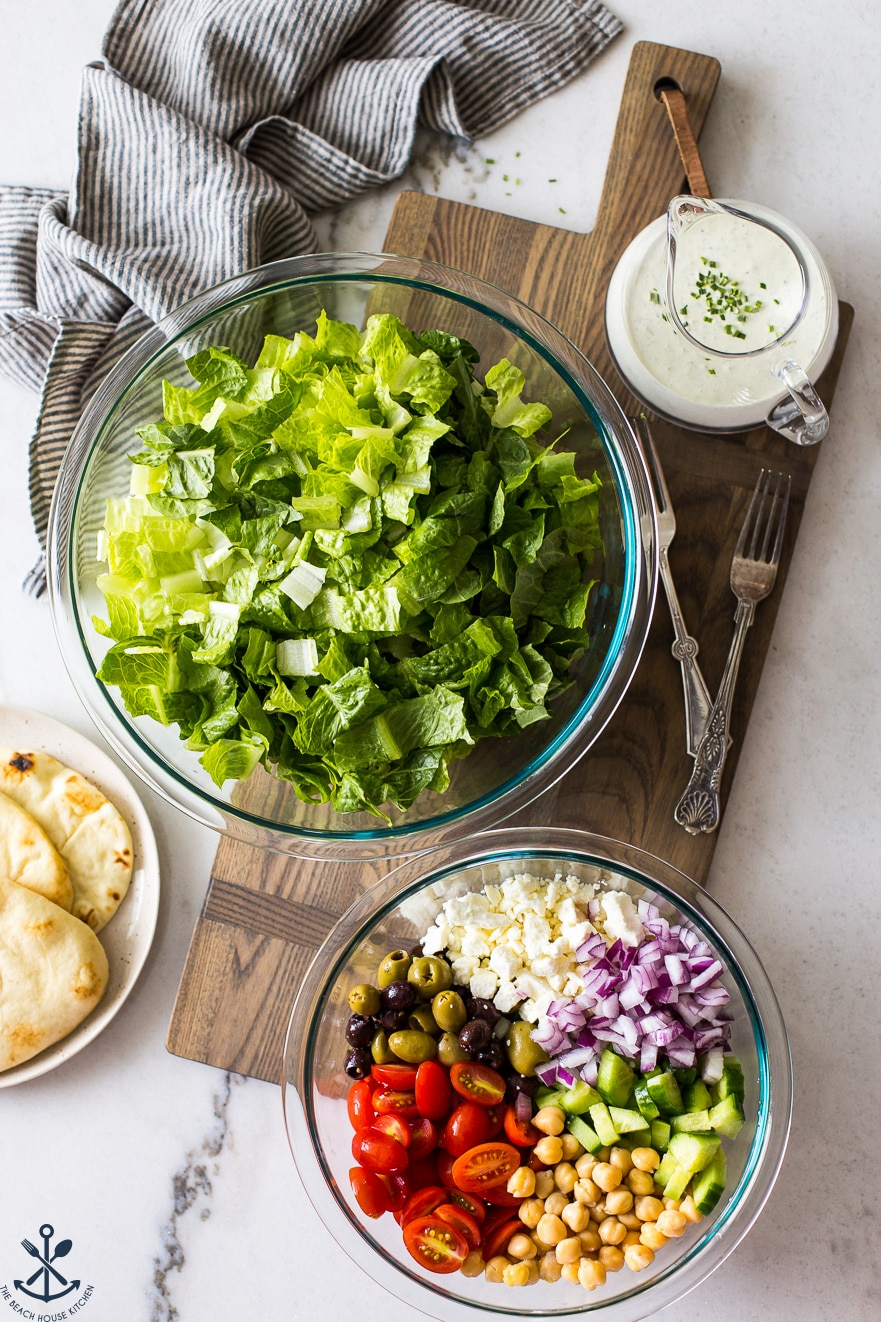 Overhead photo of bowls filled with lettuce and salad ingredients