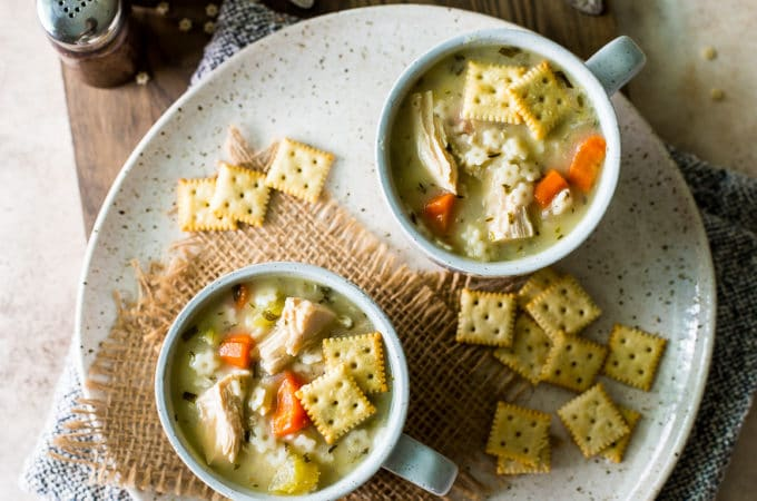 Overhead photo of two mugs filled with chicken soup with stars on a plate with saltine crackers