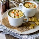 Lemony Chicken with Stars Soup in two mugs on a plate on a wooden board