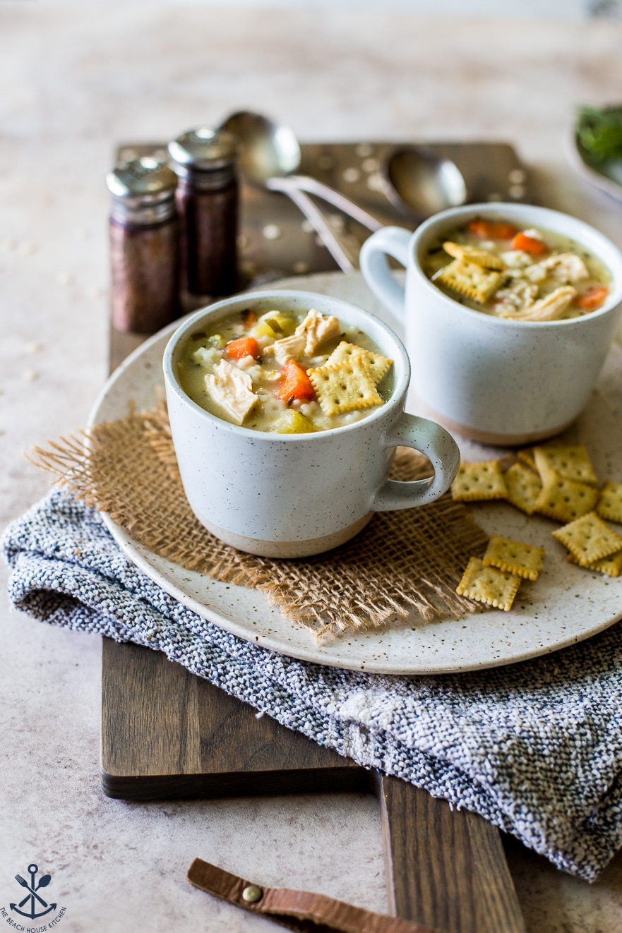Two mugs filled with chicken soup on a plate with saltines