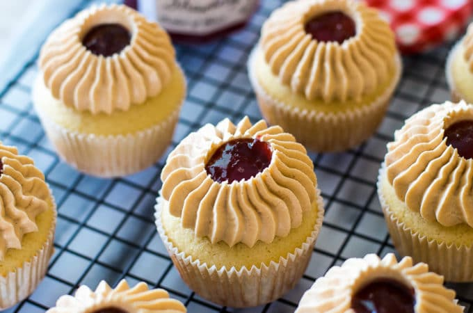 Peanut Butter and Jelly Cupcakes on a wire rack with a jar of strawberry preserves