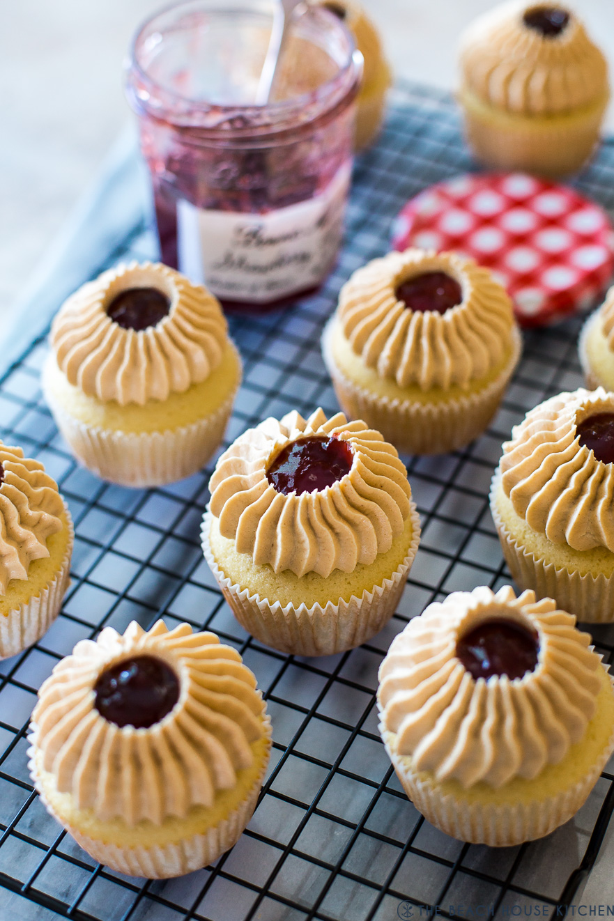 Peanut Butter and Jelly Cupcakes on a wire rack with a jar of preserves