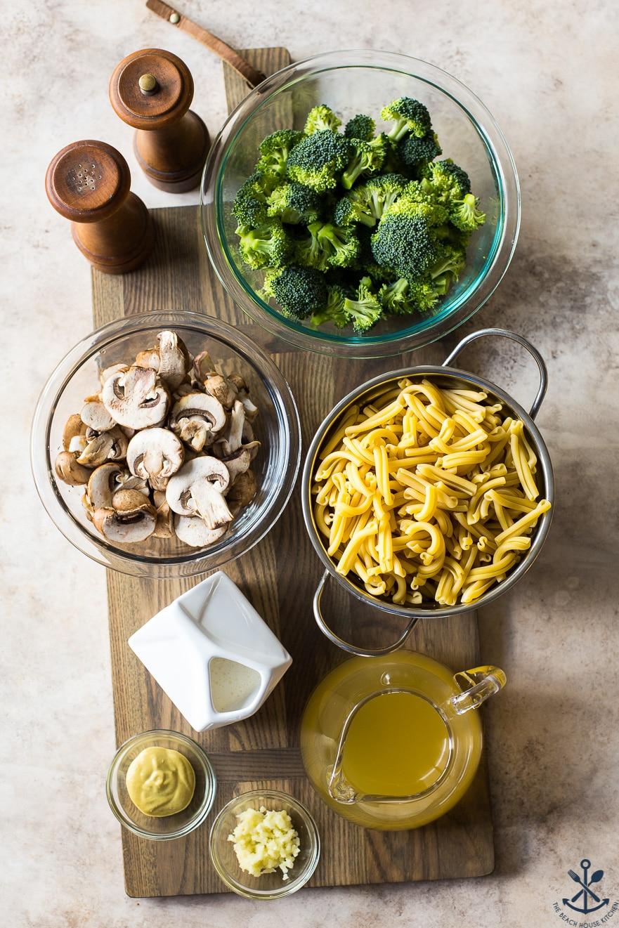 Overhead photo of ingrdeints in bowls for Creamy Garlic Broccoli Mushroom Pasta on a wooden board