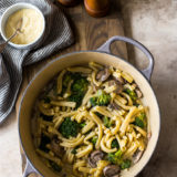 Overhead photo of a pot filled with Creamy Garlic Broccoli Mushroom Pasta on a wooden board