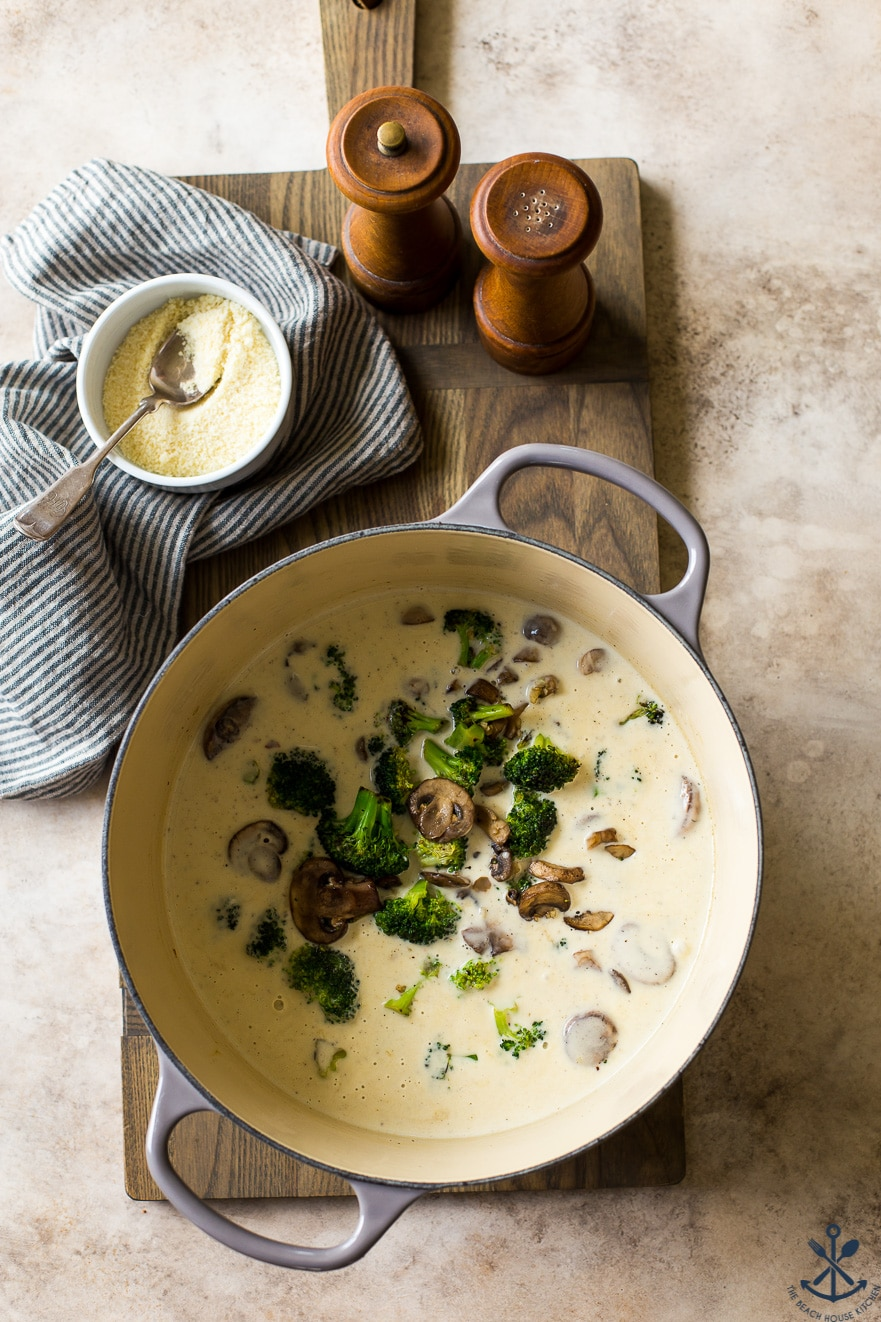 Overhead photo of pot filled with creamy sauce with mushrooms and broccoli