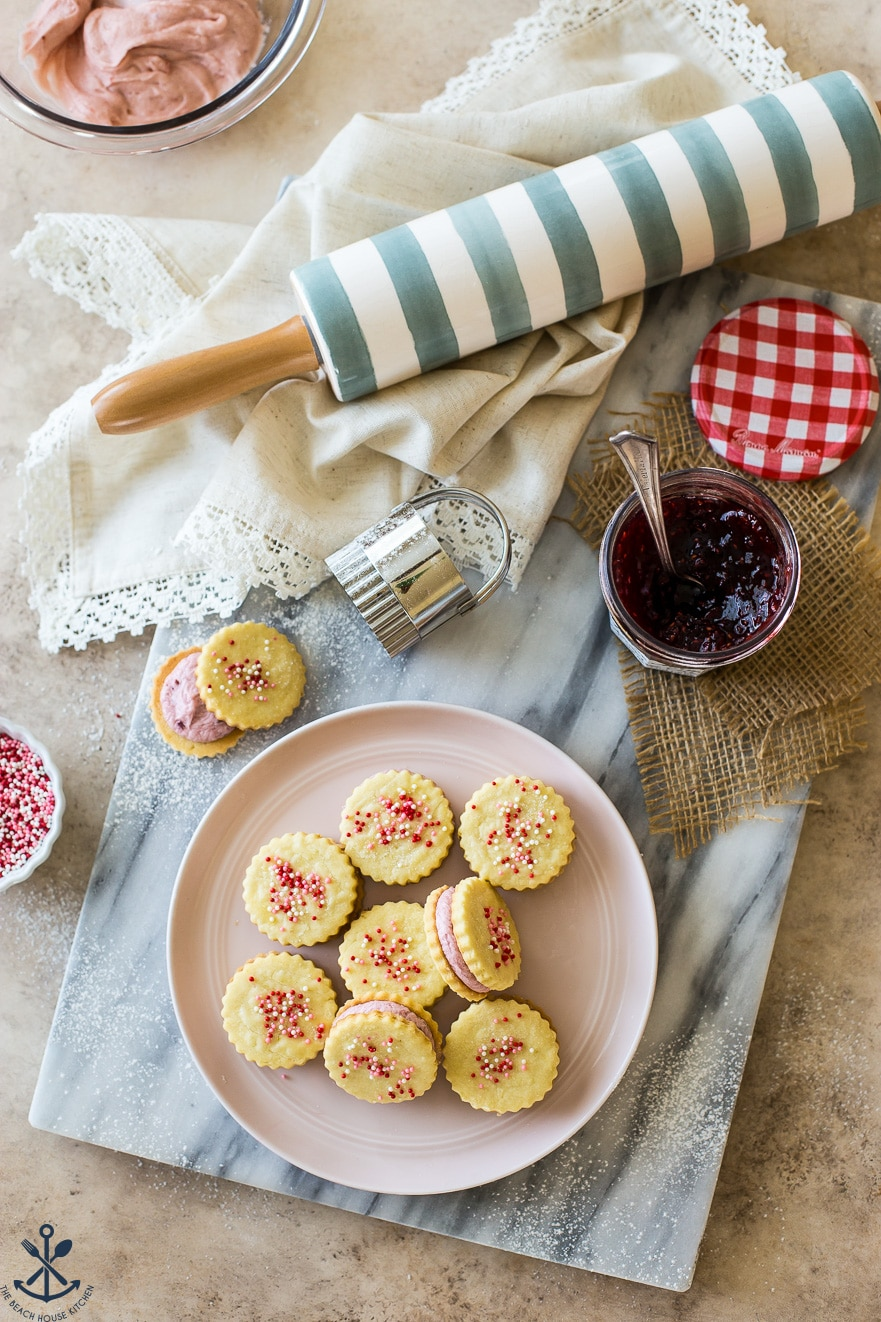 Overhead photo of a plate of Key Lime Sandwich Cookies with Raspberry Buttercream with a blue and white rolling pin and a jar of preserves