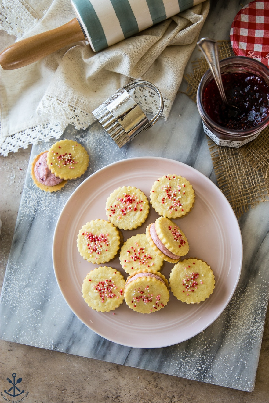 Overhead photo of Key Lime Sandwich Cookies with Raspberry Buttercream on a pink plate on a marble board