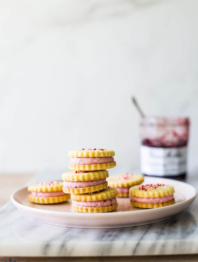 Key Lime Sandwich Cookies with Raspberry Buttercream on a pink plate on a marble board with a jar of preserves in the background