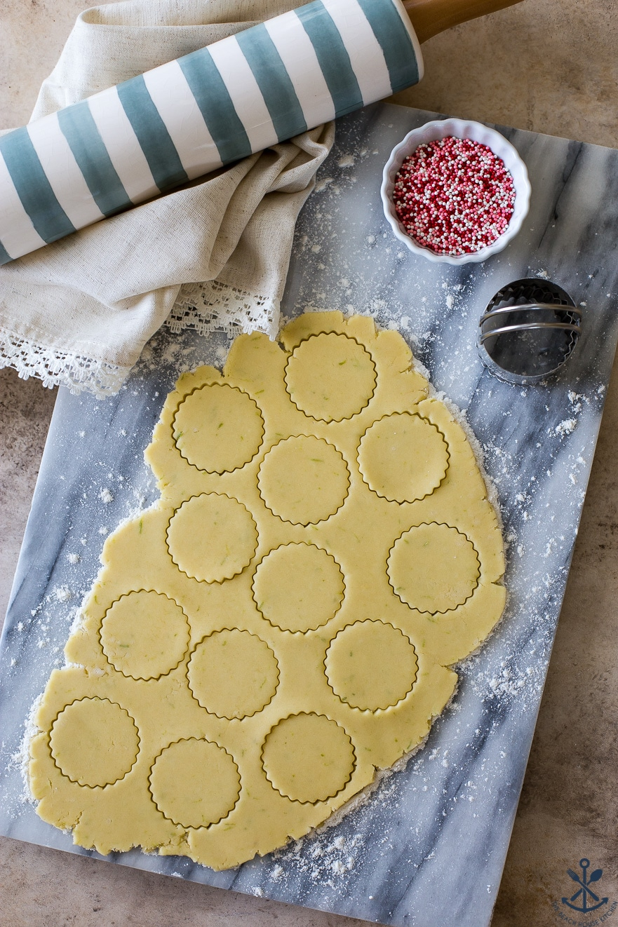 Overhead photo of round fluted cookie cutouts on a marble board with a blue and white striped rolling pin