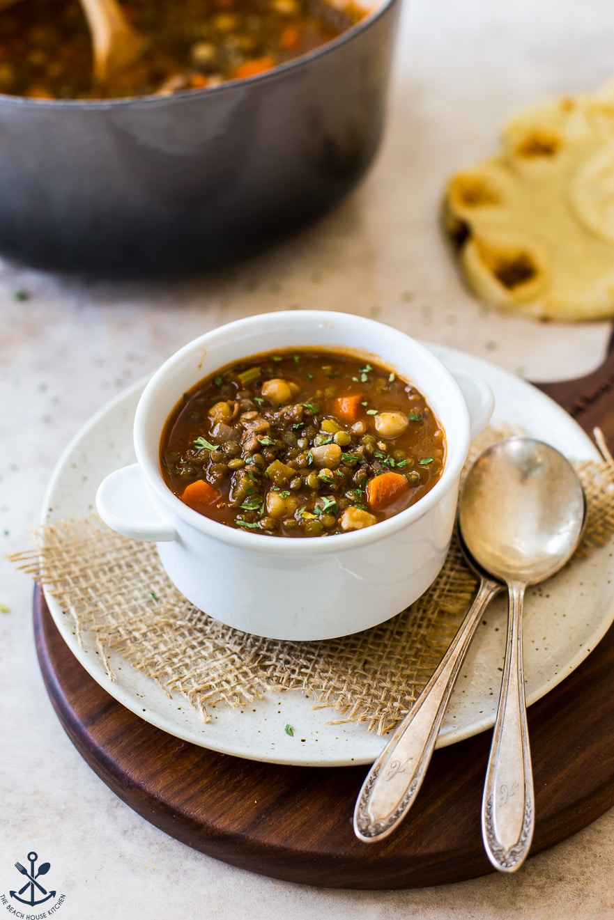 Up close photo of white bowl filled with lentil soup on a plate with two spoons