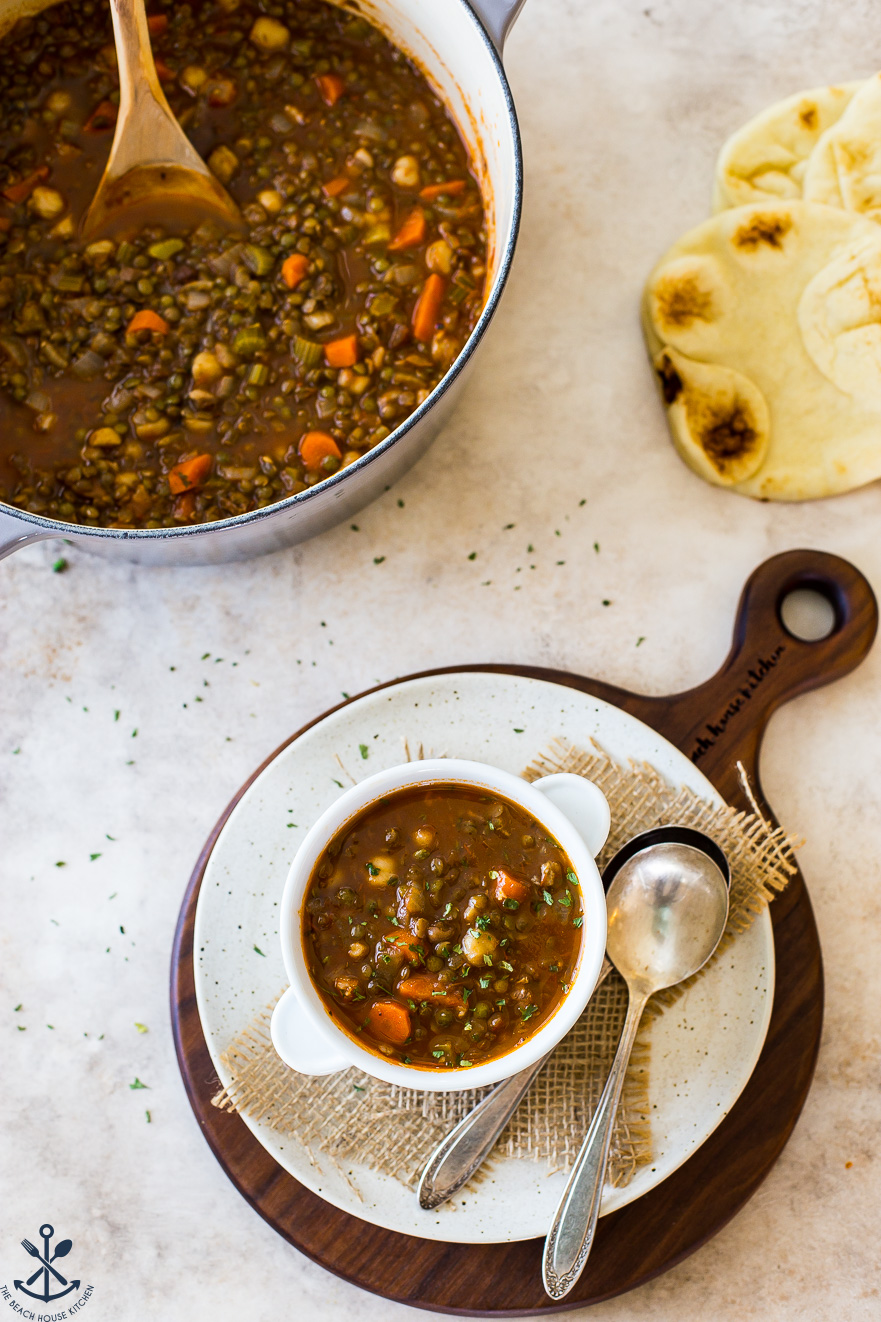 Overhead photo of a bowl of lentil soup on a round white board with a pot of soup in the background