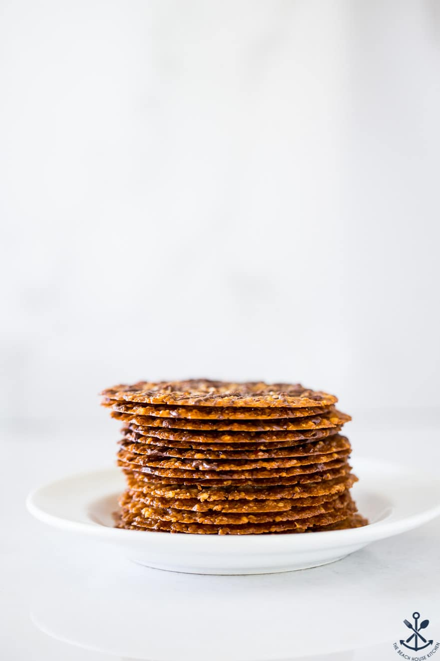 A plate with a stack of thin cookies on it