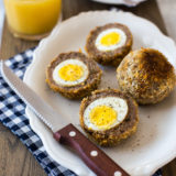 A plate with scotch eggs sliced in half with a sharp knife on a blue and white checked napkin
