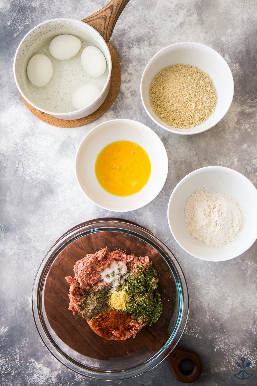 Overhead photo of ingredients for scotch eggs in bowls on a gray background