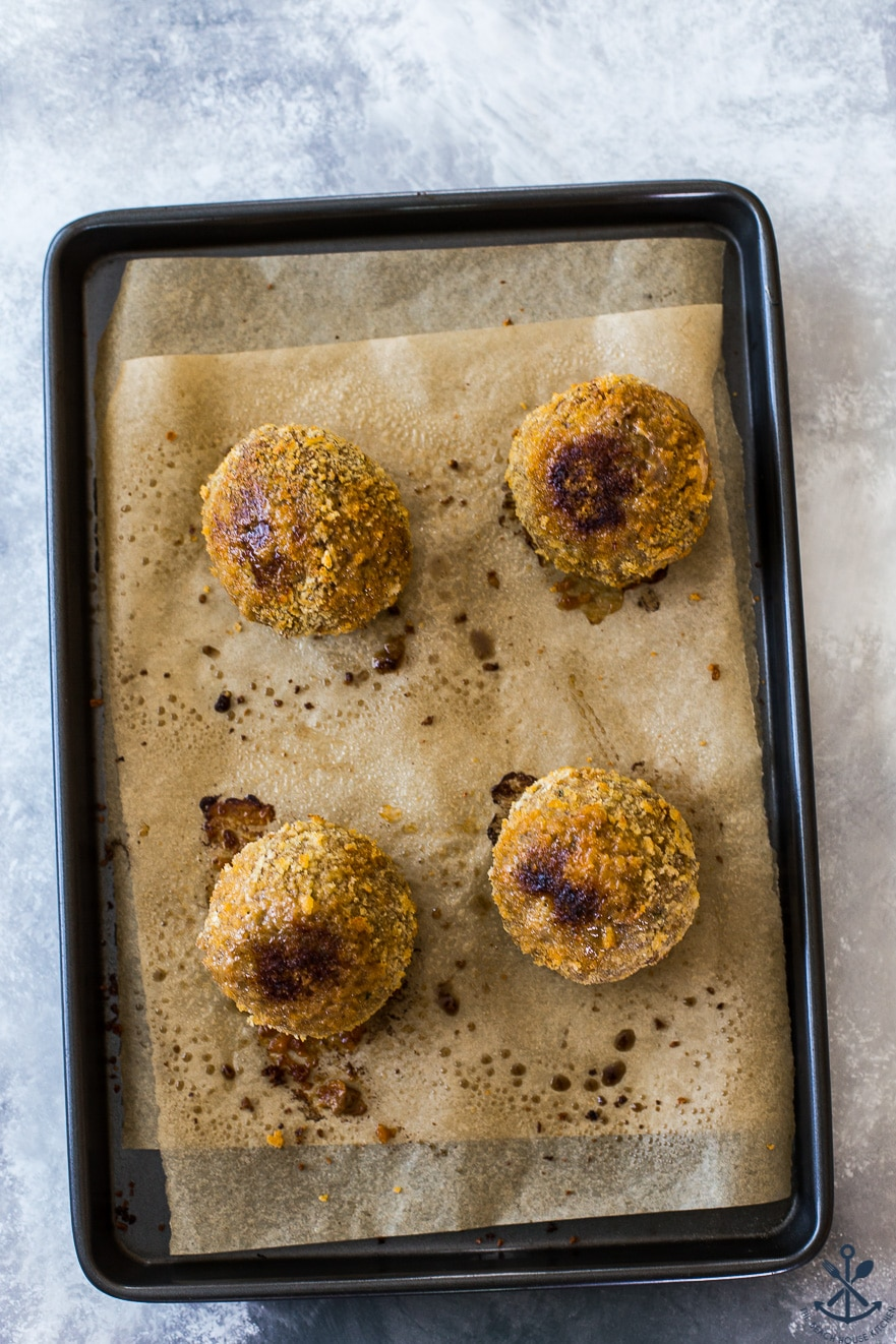 Overhead photo of 4 scotch eggs on a baking sheet lined with parchment paper
