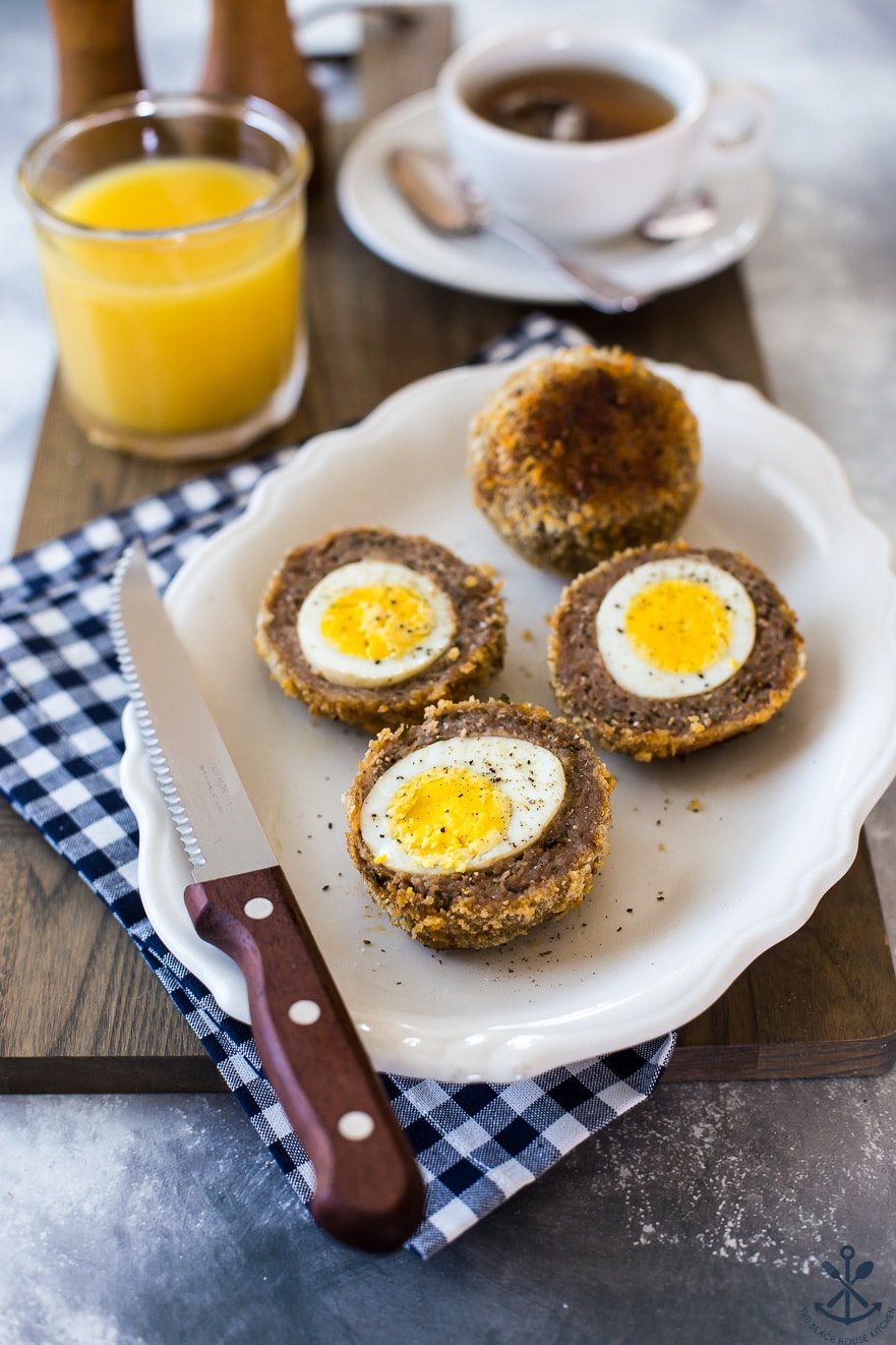 A plate of halved scotch eggs with a knife on a blue and white checked napkin