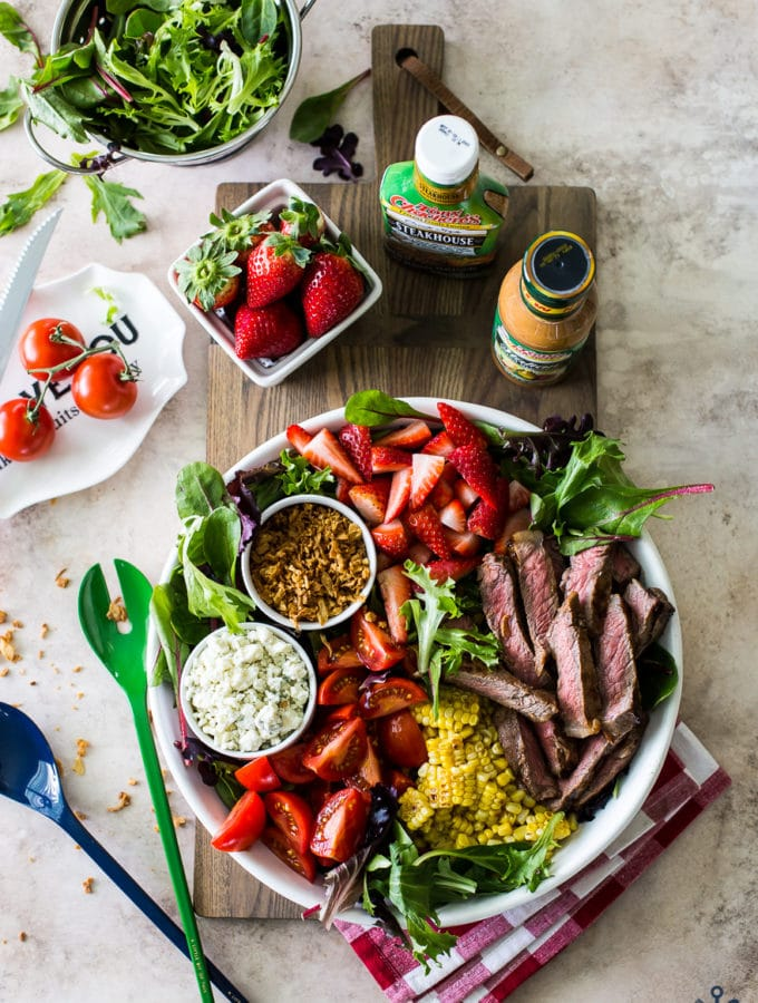 Overhead photo of a steak salad with corn and strawberries