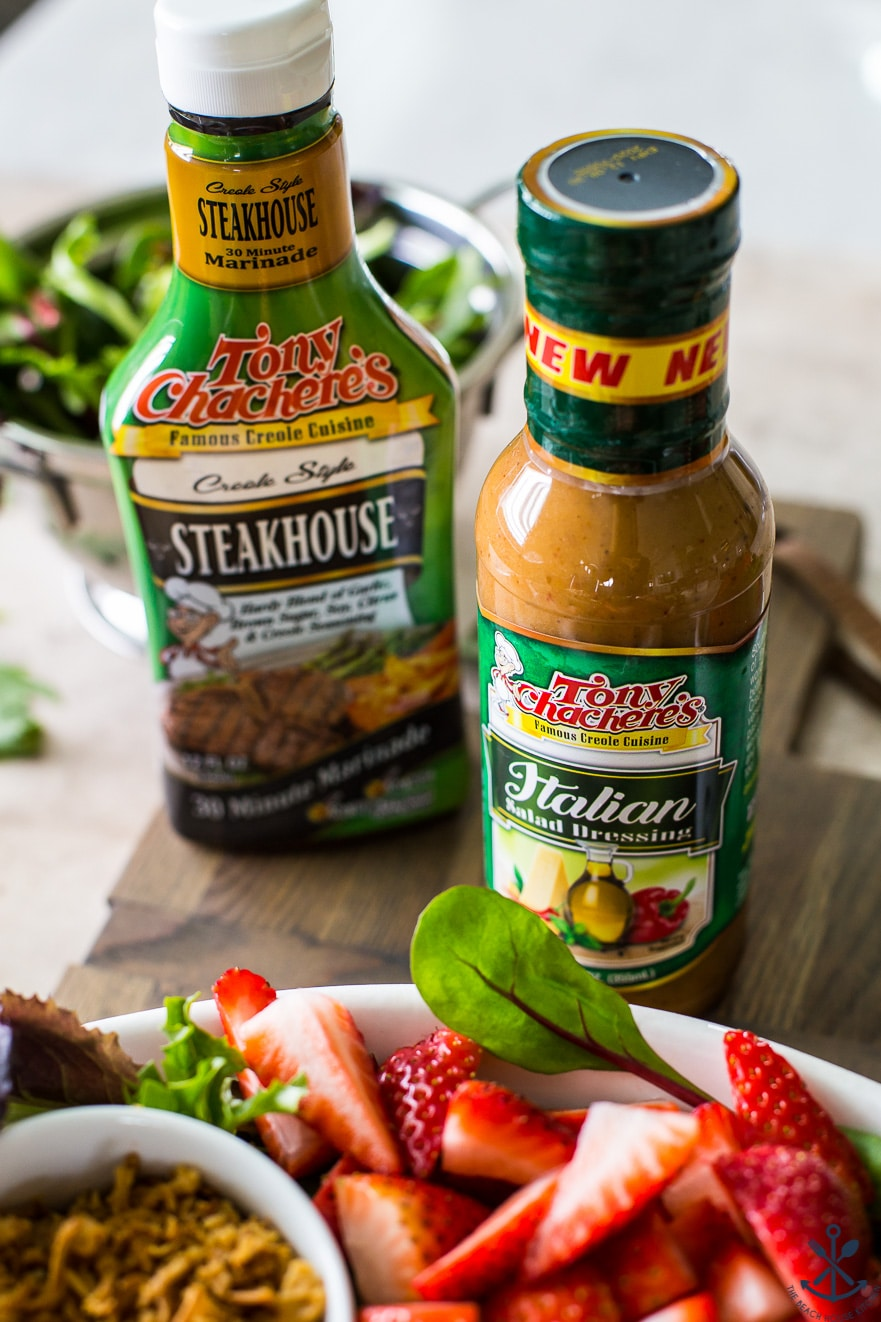 A bottle of Italian dressing with a bottle of steakhouse marinade in the background