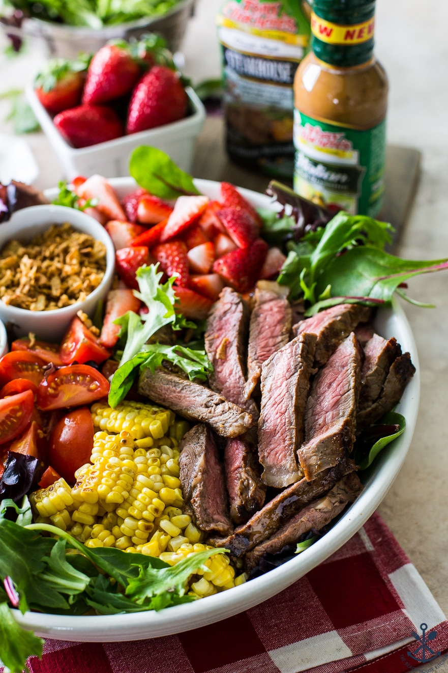 A Zesty Grilled Steak Salad with Corn and Strawberries in a white round bowl