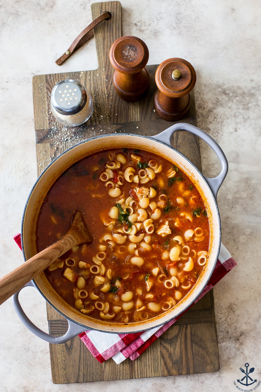 Overhead photo of chicken parm soup in a large pot on a wooden board