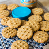 Classic Peanut Butter Cookies on a wire rack with a jar of peanut butter and a bright blue lid