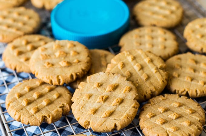 Peanut butter cookies on a wire rack with a jar of Skippy peanut butter and a blue lid