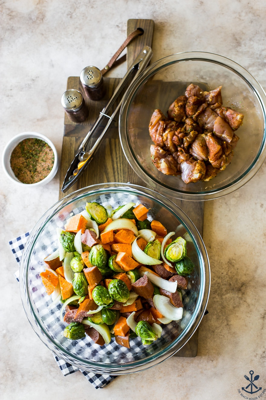 Overehad photo of bowl of veggies and bowl of uncooked chicken